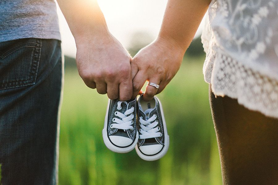Parents holding hands and baby shoes